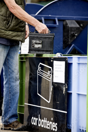A senior man recycling a car battery, close-up