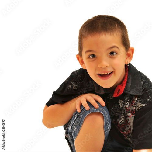 Boy sitting with hand on knee smiling