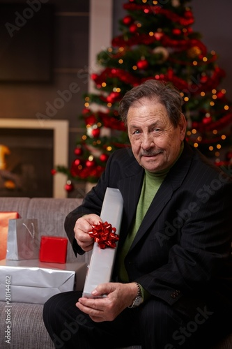 Senior man wrapping presents at christmas