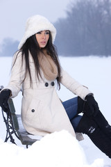 Beautiful and sexy woman sitting on bench in snowy outdoors
