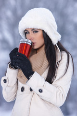 Beautiful woman holding thermal mug in snowy winter outdoors