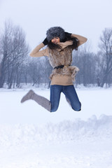 Young Jumping woman in snowy winter outdoors