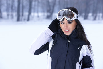 Beautiful woman wearing goggles in snowy winter outdoors