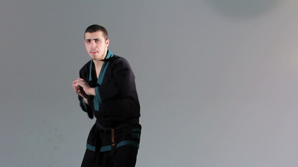 Karate master shows exercise with nunchaku