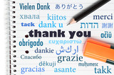 Thank you in many different languages written on an open noteboo