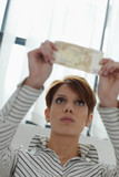 woman checking banknote watermark poster