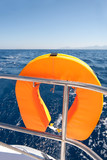 Orange lifebuoy on sailing ship