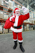 Santa Claus with red sack ringing in a bell in storehouse