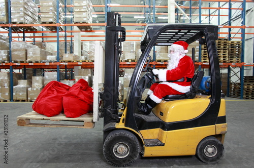 Santa Claus as a forklift operator at work in warehouse - 28161032