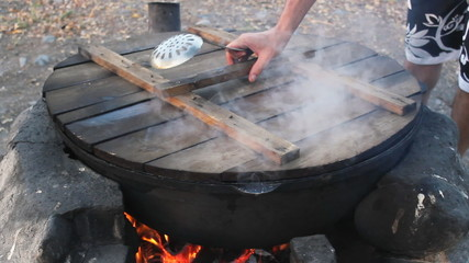 Kettle with cooking meat over burning campfire.