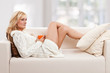 Beauty, blondie woman in a sofa with an orange coloured cup