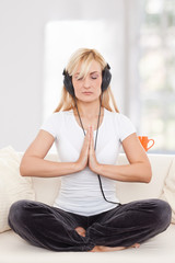 Beauty, blondie woman in a yoga position listening music