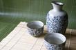 Sake set on bamboo pad and green background