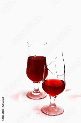 two glasses with wine and drops  .one  glass is broken
