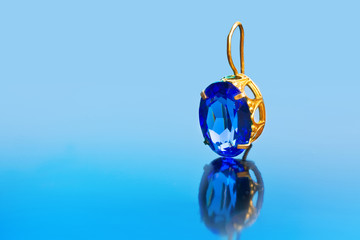 Earring with reflection on a blue background