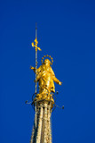 Holy Mary statue on top of Milan Dome in the blue sky