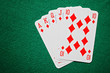 Royal straight flush poker cards on a green table background