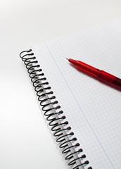 boligrafo rojo encima de un cuaderno