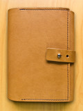 leather case notebook on wood background