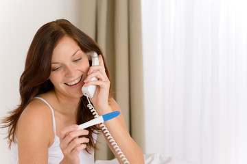 Pregnancy test - happy woman on phone