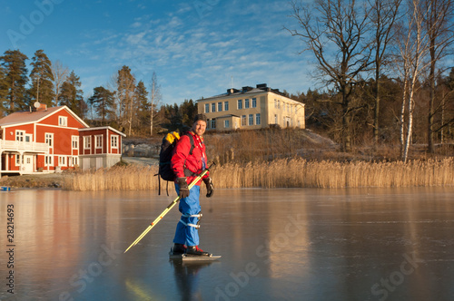 A male ice skater on a frozen lake
