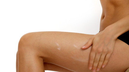 Woman applying moisturizer cream on thigh