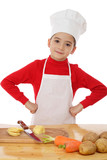 Smiling little chief-cooker on the desk with vegetables poster