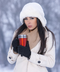 Beauty on snowy outdoors with thermal mug
