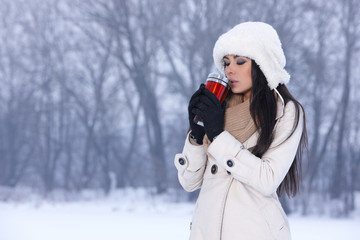 Woman drinking hot coffee from thermal mug