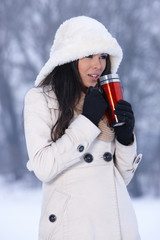 Woman holding thermal mug with hot drink