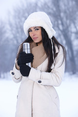 Beauty on snowy outdoors holding thermos