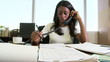 Young businesswoman working at desk and talking on phone