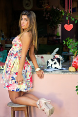 beautiful young blond model in flowery dress on stool