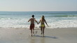 Young couple running into the ocean waves at the beach