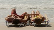 Young couple on lounge chairs holding hands by the ocean