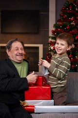 Boy giving christmas present to grandfather