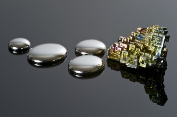 Droplets of mercury and bismuth on a reflective surface.