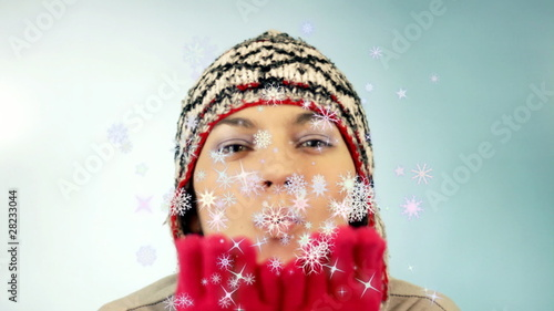 Woman in winter hat blowing snowflakes