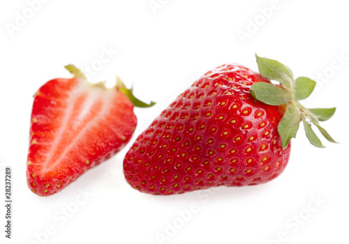 Cut and whole strawberry on white background