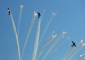 Propeller planes firing flares during an air show.