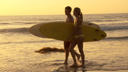 Young couple walking with surfboards on beach at sunset