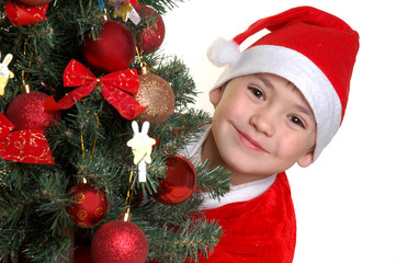 The boy in a suit of Santa Claus under a fur-tree