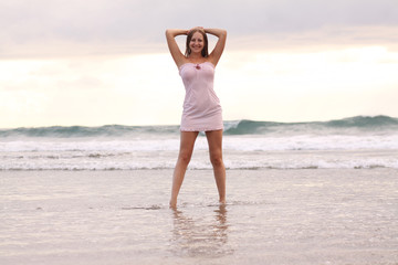 young woman in pink dress at the beach