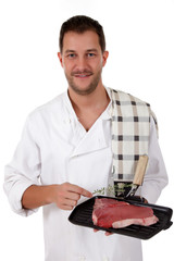 Young attractive caucasian male cook, t-bone steak