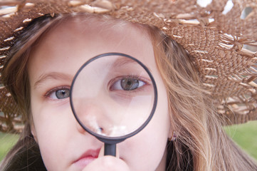 Girl with magnifying glass explores the nature of
