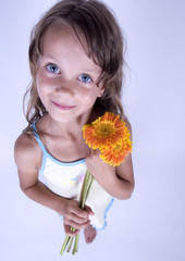 A little girl holding in her hand a beautiful flower