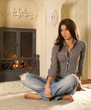A young and cute brunette is sitting near the fireplace