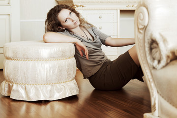 Beautiful woman leaning on the ottoman.