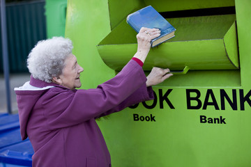 A senior woman recycling a book