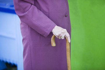 A senior woman holding a walking stick, close-up